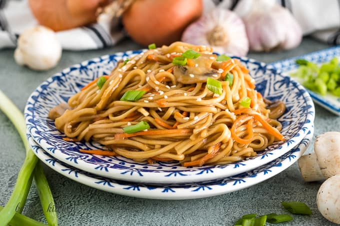 A blue and white plate with a serving of vegetable lo mein.