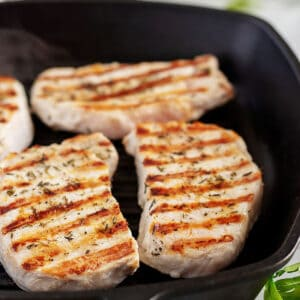 Four grilled pork chops in a cast iron skillet.