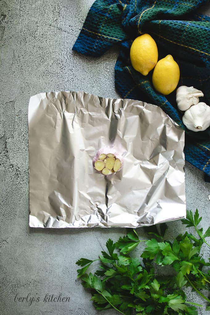A whole bulb of garlic with the cloves exposed on foil.