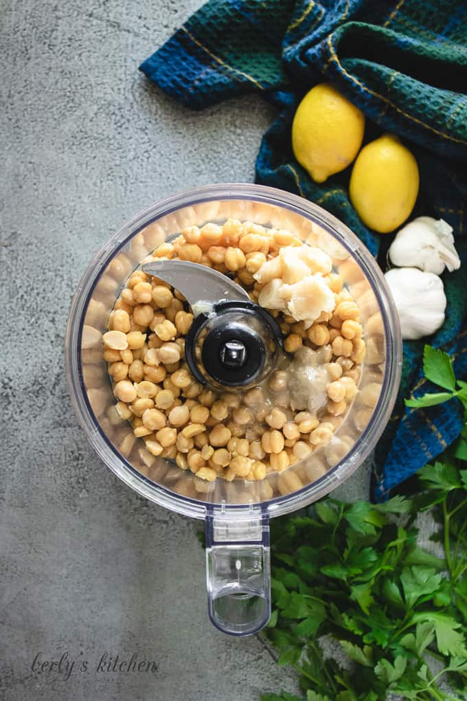 Chickpeas, tahini, and other ingredients in a food processor.