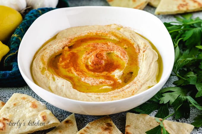 A bowl of hummus surrounded by homemade flatbread.