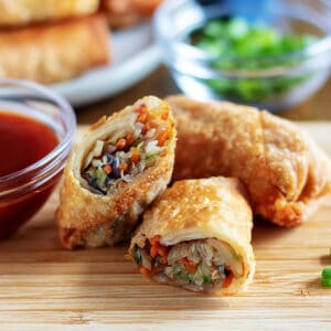 Egg rolls on a cutting board with dipping sauce.