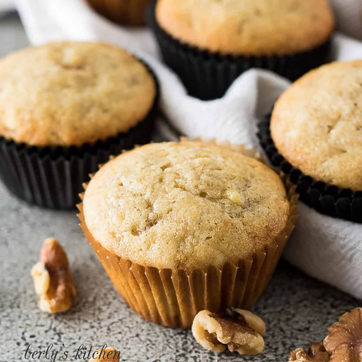 Banana nut muffins in brown and black muffin liners.