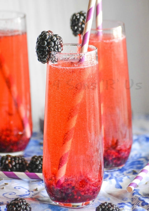 The blackberry lavender champagne cocktail in a tall glass.