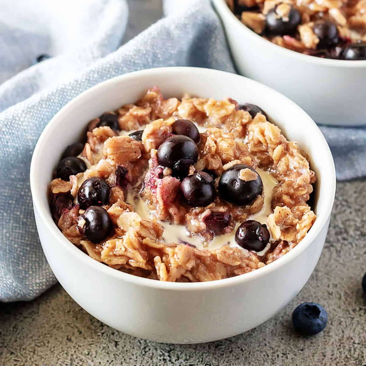 Two bowls of blueberry oatmeal topped with fresh blueberries.