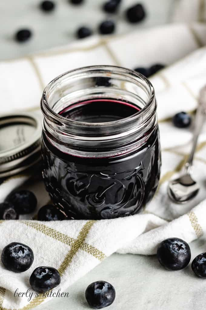 The finished syrup in a jar surrounded by fresh blueberries.