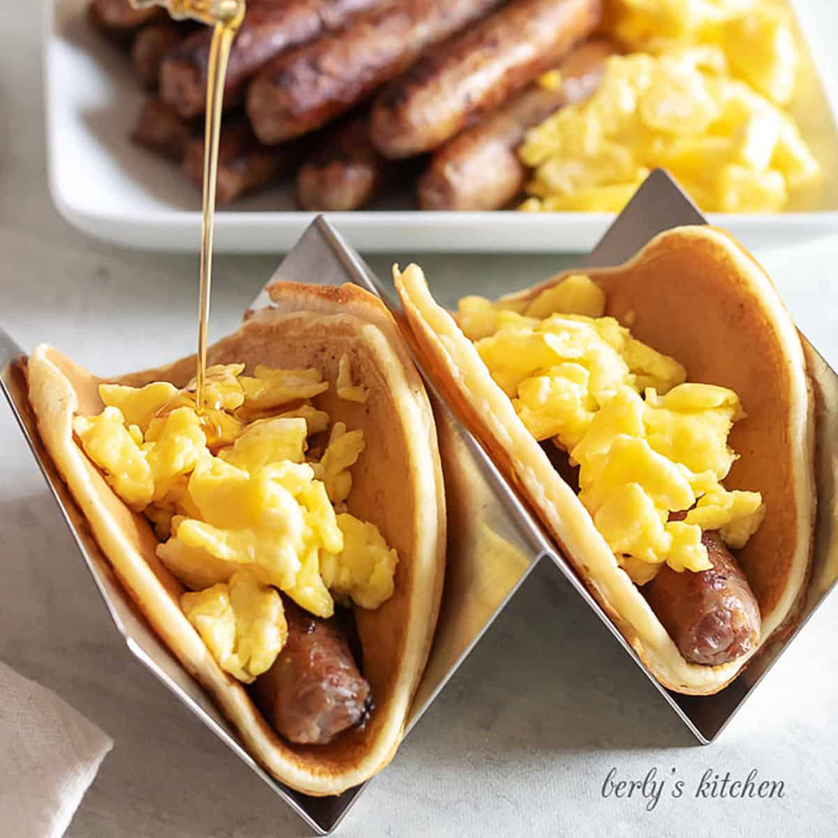 Two pancake breakfast tacos filled with sausage links and scrambled eggs being topped with syrup.