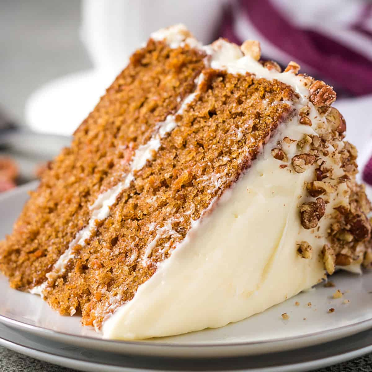 Slice of homemade carrot cake with pecans laying on its side.