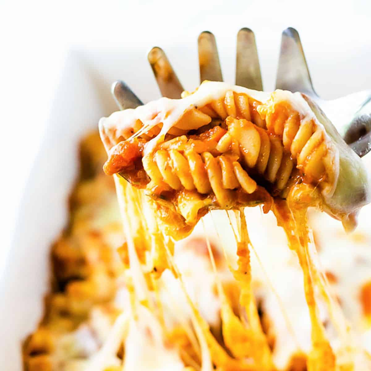 Cheesy pasta bake on a pasta scoop.