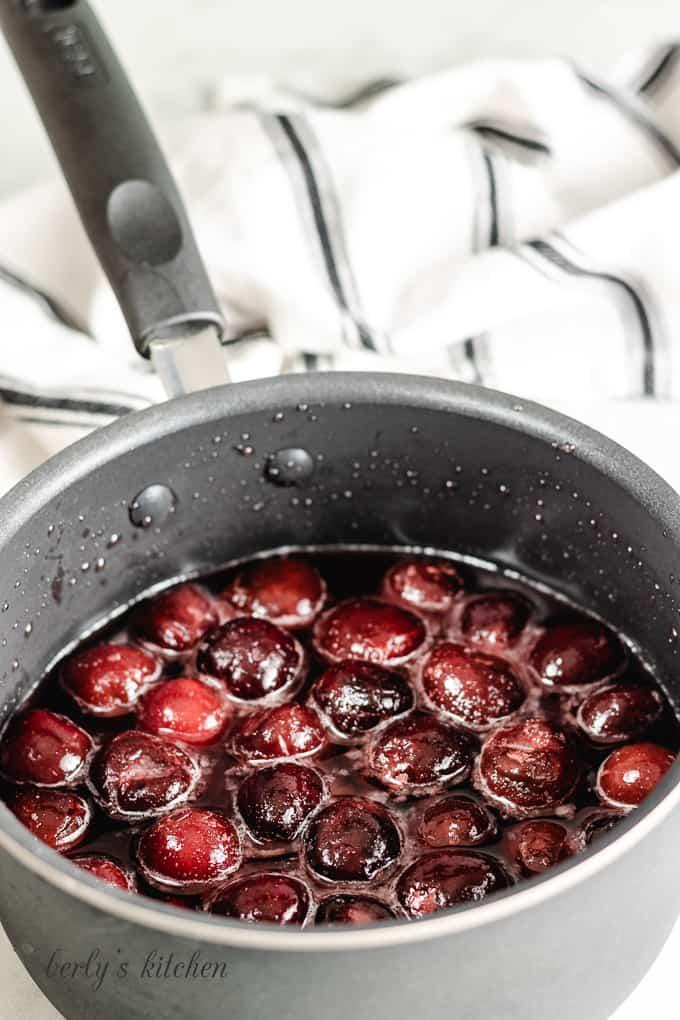 Cherries, water, sugar, a lemon juice in a saucepan.