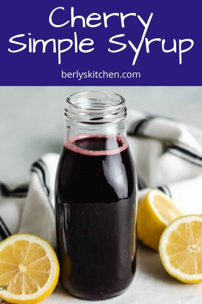Cherry simple syrup in a bottle surrounded by halved lemons.