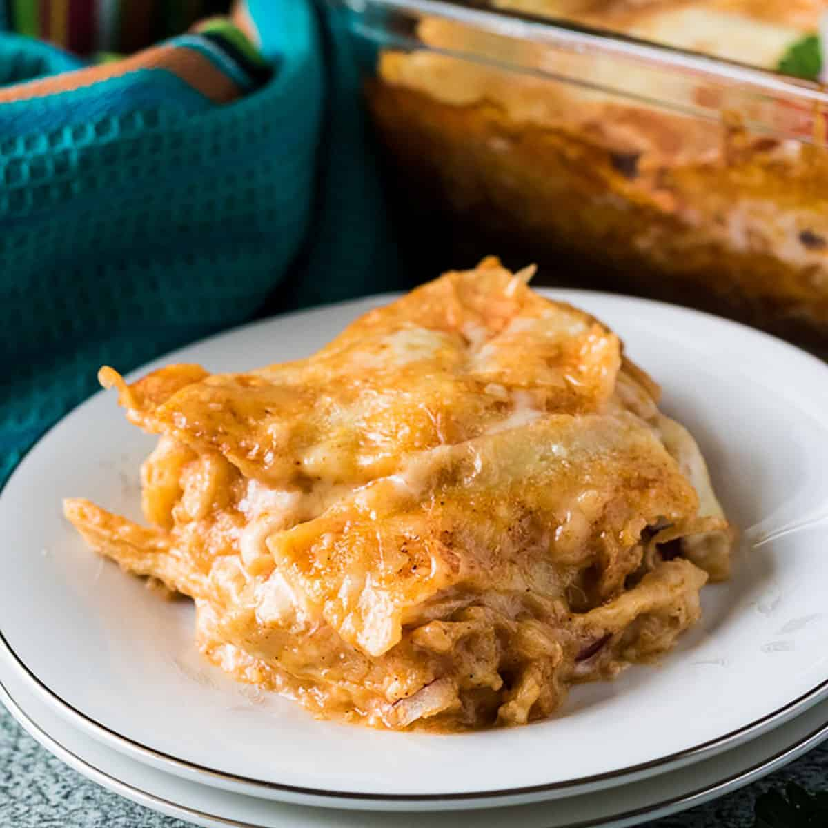 Chicken enchilada casserole on a white plate.