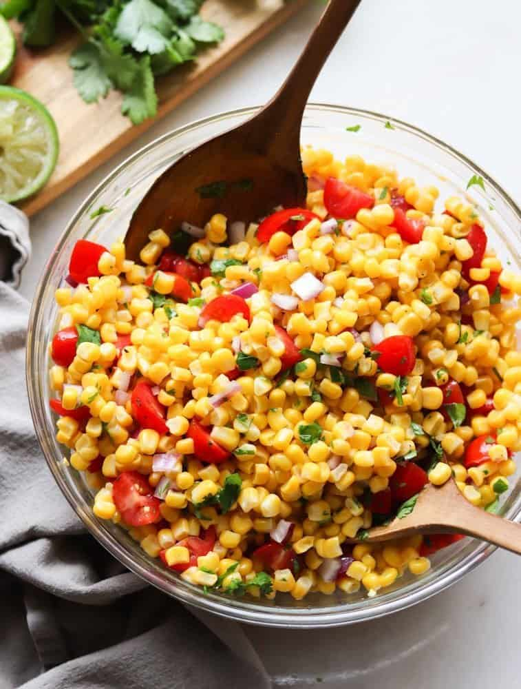 Two wooden spoons in a bowl of the corn salad.