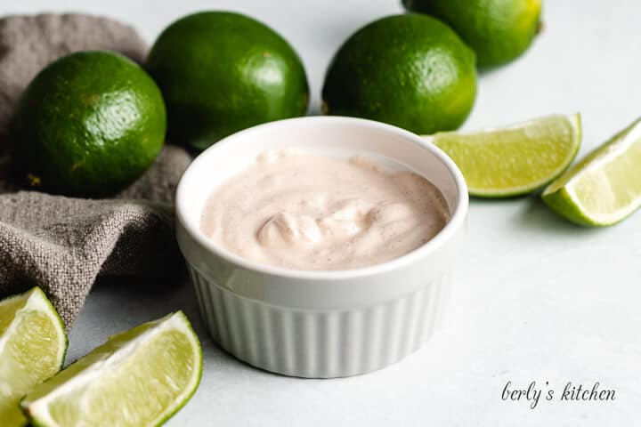 The chipotle cream sauce in a ramekin accented with limes.