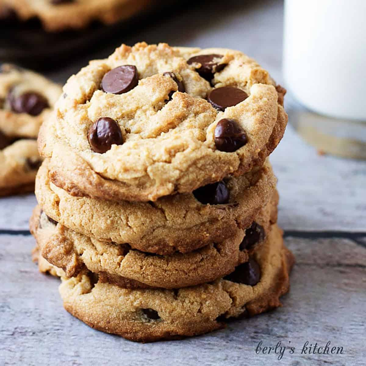 Stack of peanut butter cookies with chocolate chips in front of a cup of milk.