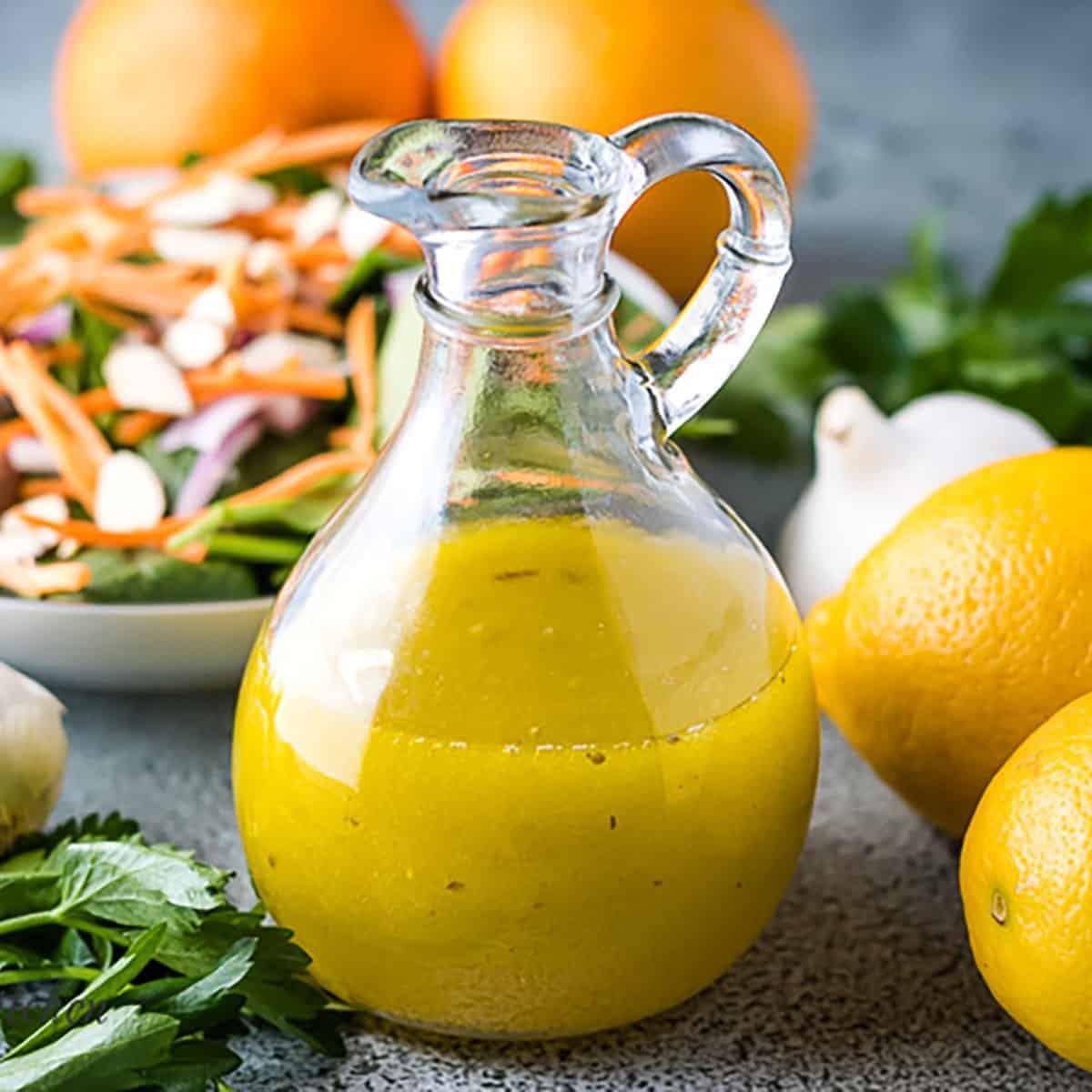 Citrus vinaigrette dressing next to two lemons and garlic.