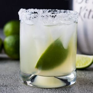 Margarita with a lime in a salt-rimmed cocktail glass.