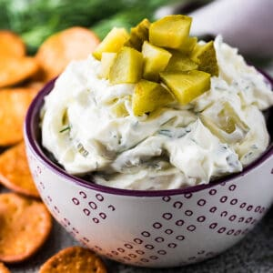 Dill pickle dip topped with chopped pickles in a small bowl.