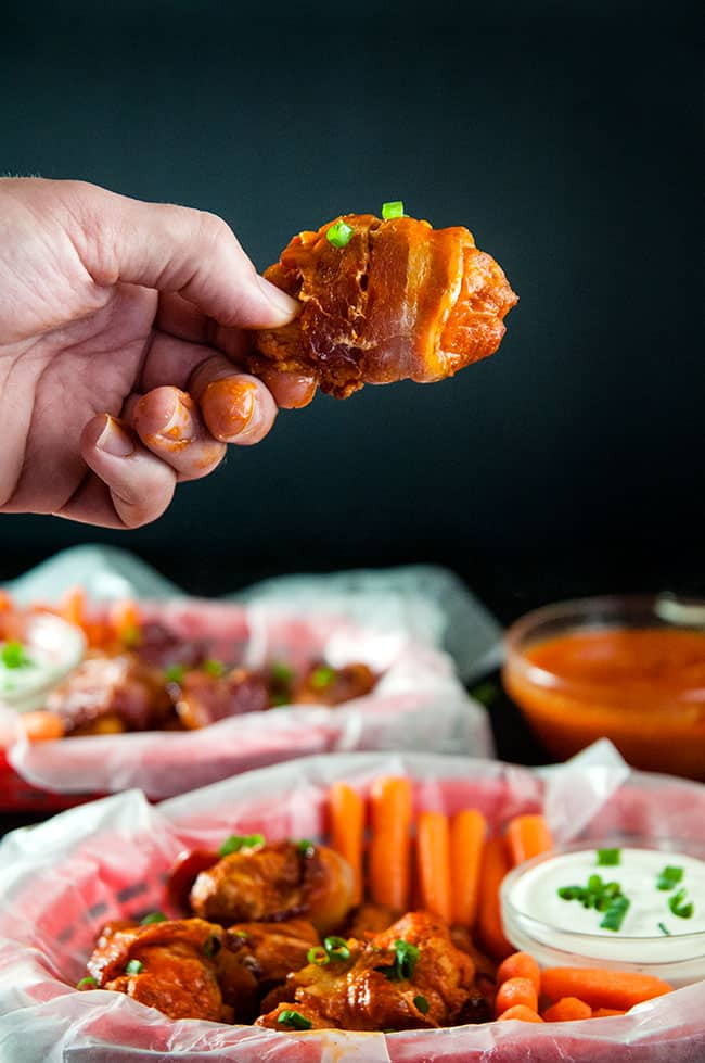 A buffalo wing, wrapped in bacon, being lifted from the plate by a hand.
