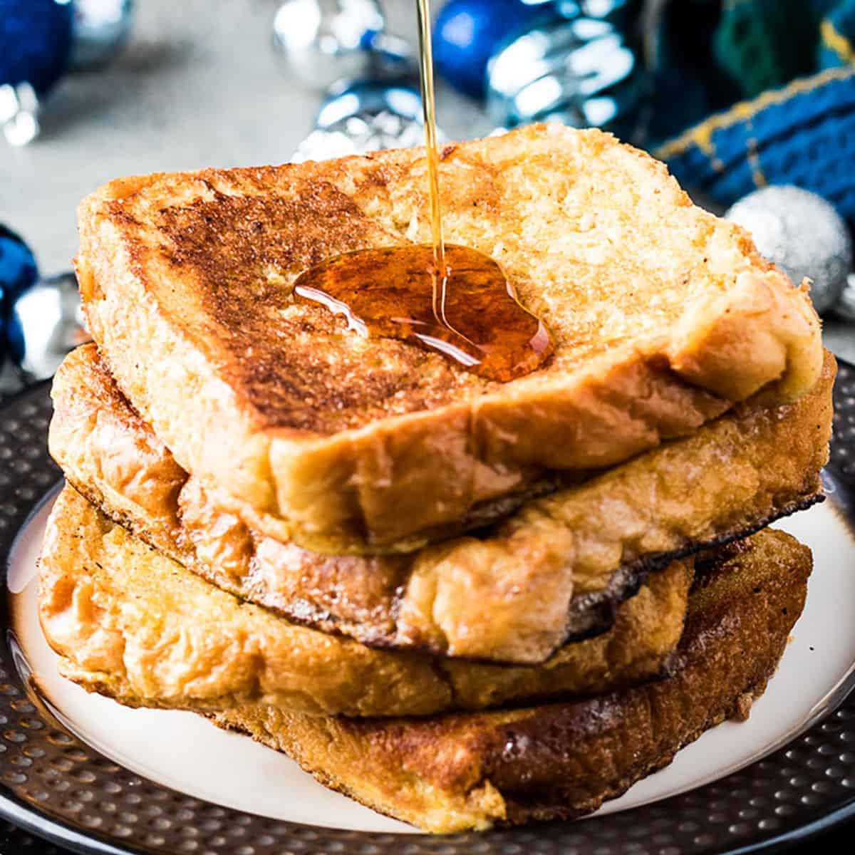 Stack of eggnog French toast being drizzled with syrup.