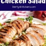 Two grilled and sliced chicken breasts over a bed of lettuce.