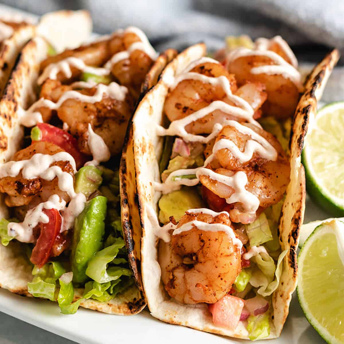 Two grilled shrimp tacos drizzled with chipotle sauce.