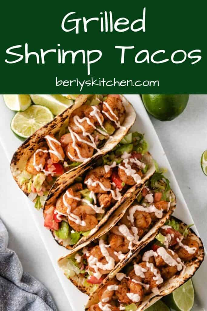 Aerial view of four shrimp tacos served with fresh lime wedges.