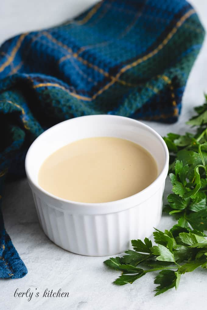 The salad dressing served in a small white ramekin.