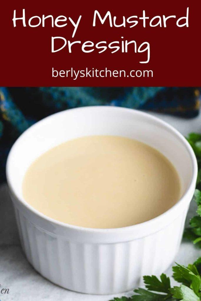 Half a cup of honey mustard salad dressing in a ramekin.