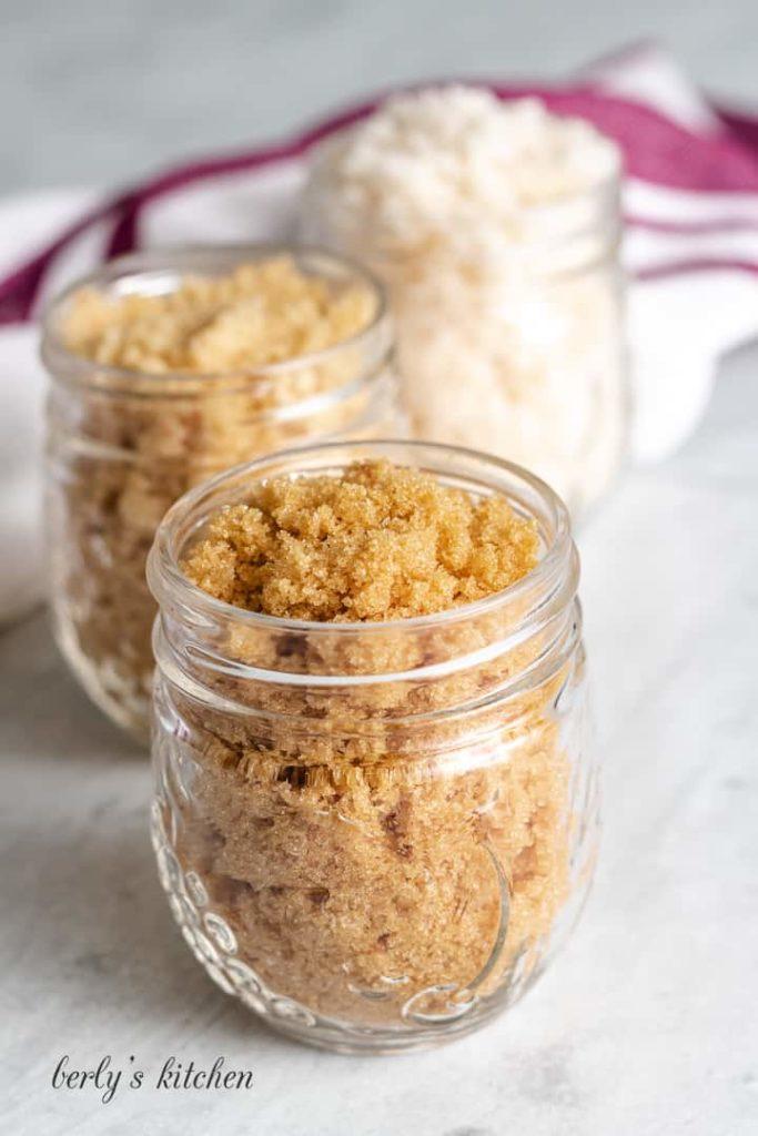 Light, dark, and maple syrup sugars in mason jars.