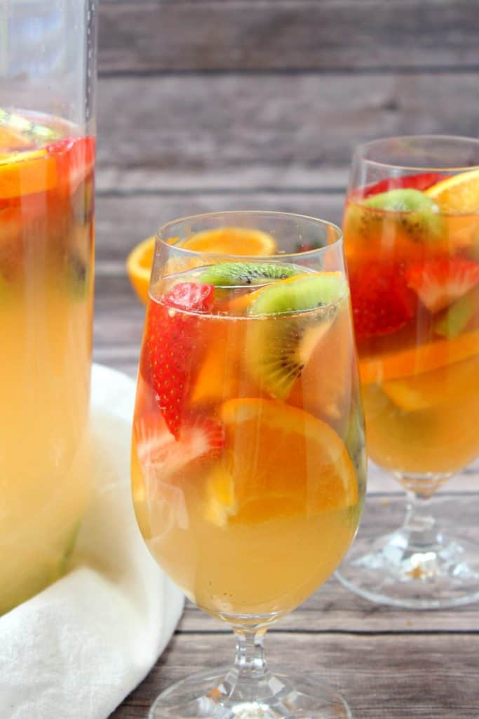 The sangria served in a stemmed cocktail glass with fresh tropical fruit.