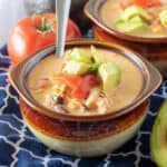 Bowl of Instant Pot Chicken Taco Soup with tomatoes and fresh avocado.