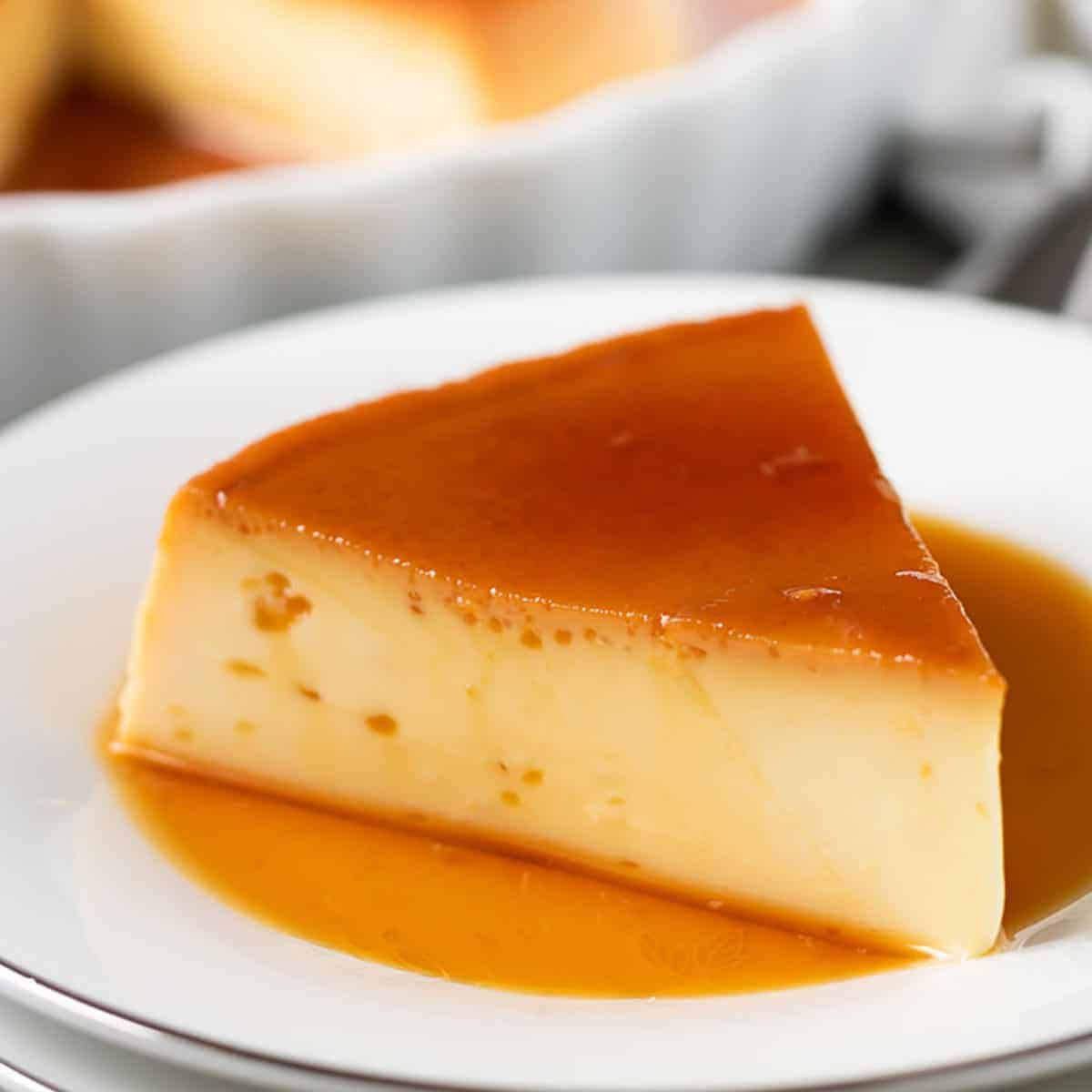 Instant Pot flan slice with caramel sauce on a white plate.