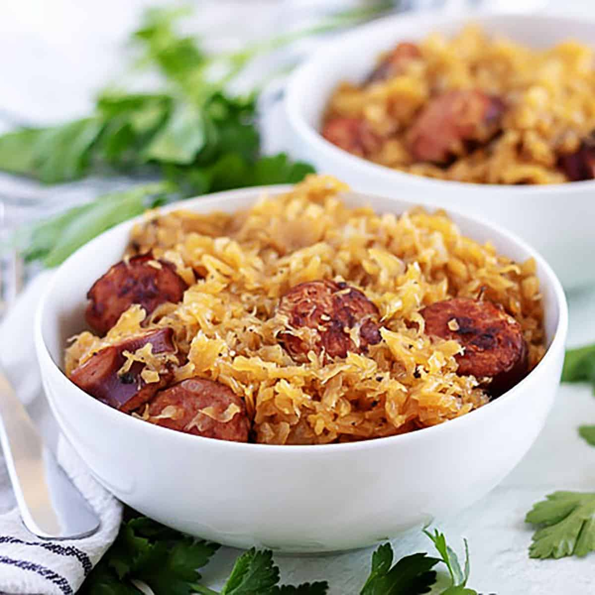 White bowl filled with sauerkraut and sauteed kielbasa sausage.