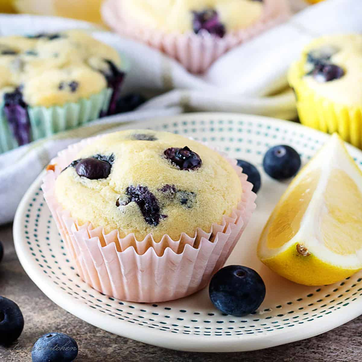 Lemon blueberry muffin on a plate with a slice of lemon and fresh blueberries.
