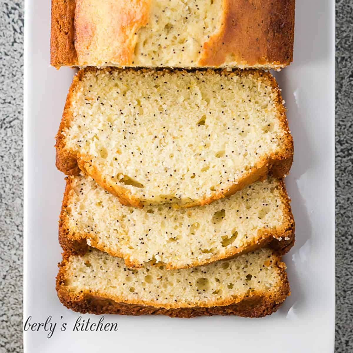 Top down view of lemon poppy seed bread on a white platter.