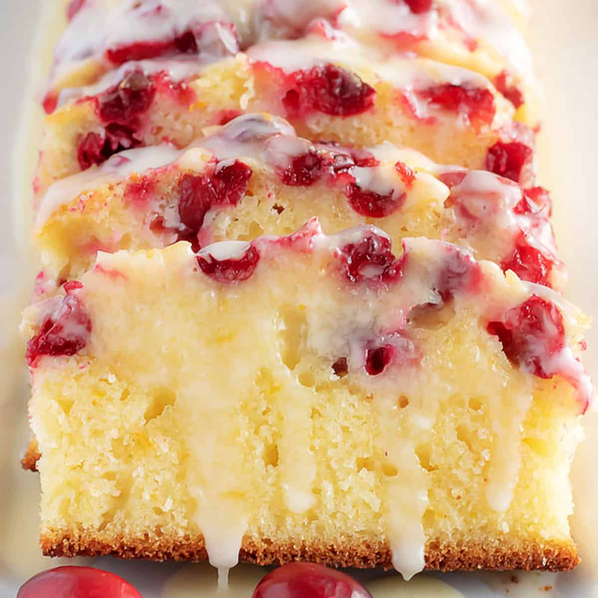 Sliced orange cranberry bread with glaze.