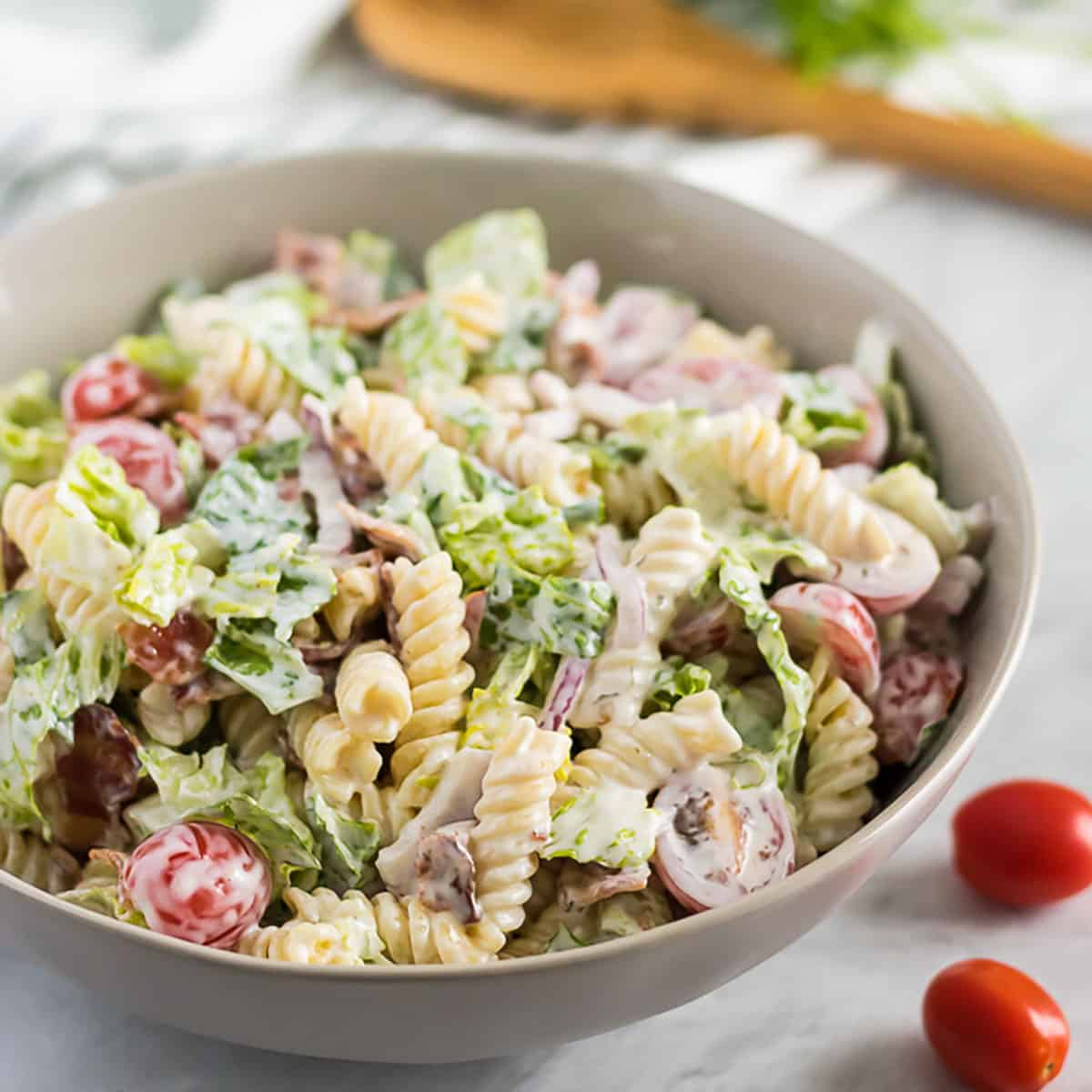 Bowl of BLT pasta salad next to a wooden spoon and tomatoes.