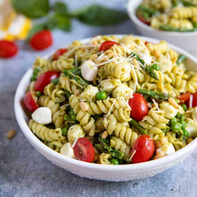 The pesto pasta salad topped with mozzarella cheese and tomatoes.