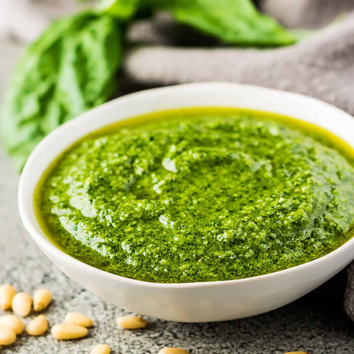 Small bowl of pesto sauce with fresh pine nuts.