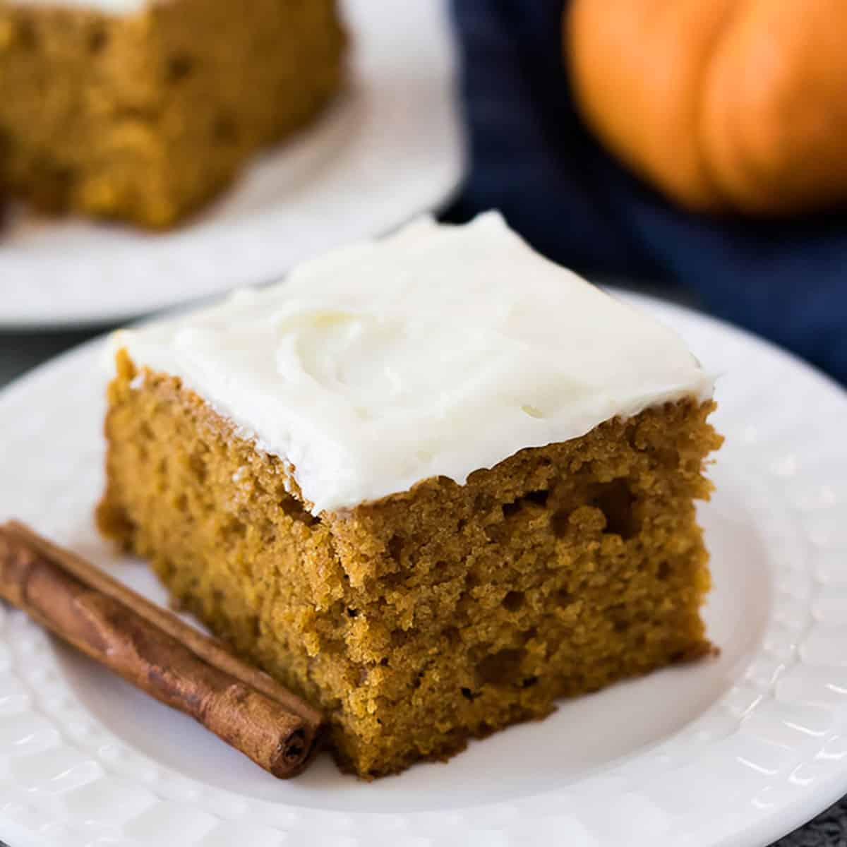 Pumpkin cake next to a cinnamon stick on a small white plate.