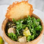 Close up of a bowl of roasted brussel sprouts Caesar salad with a Parmesan crisp.
