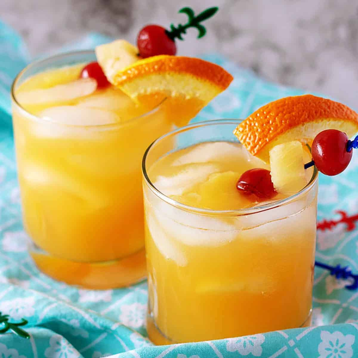 Two orange rum drinks in cocktail glasses with oranges and cherries for garnishes.