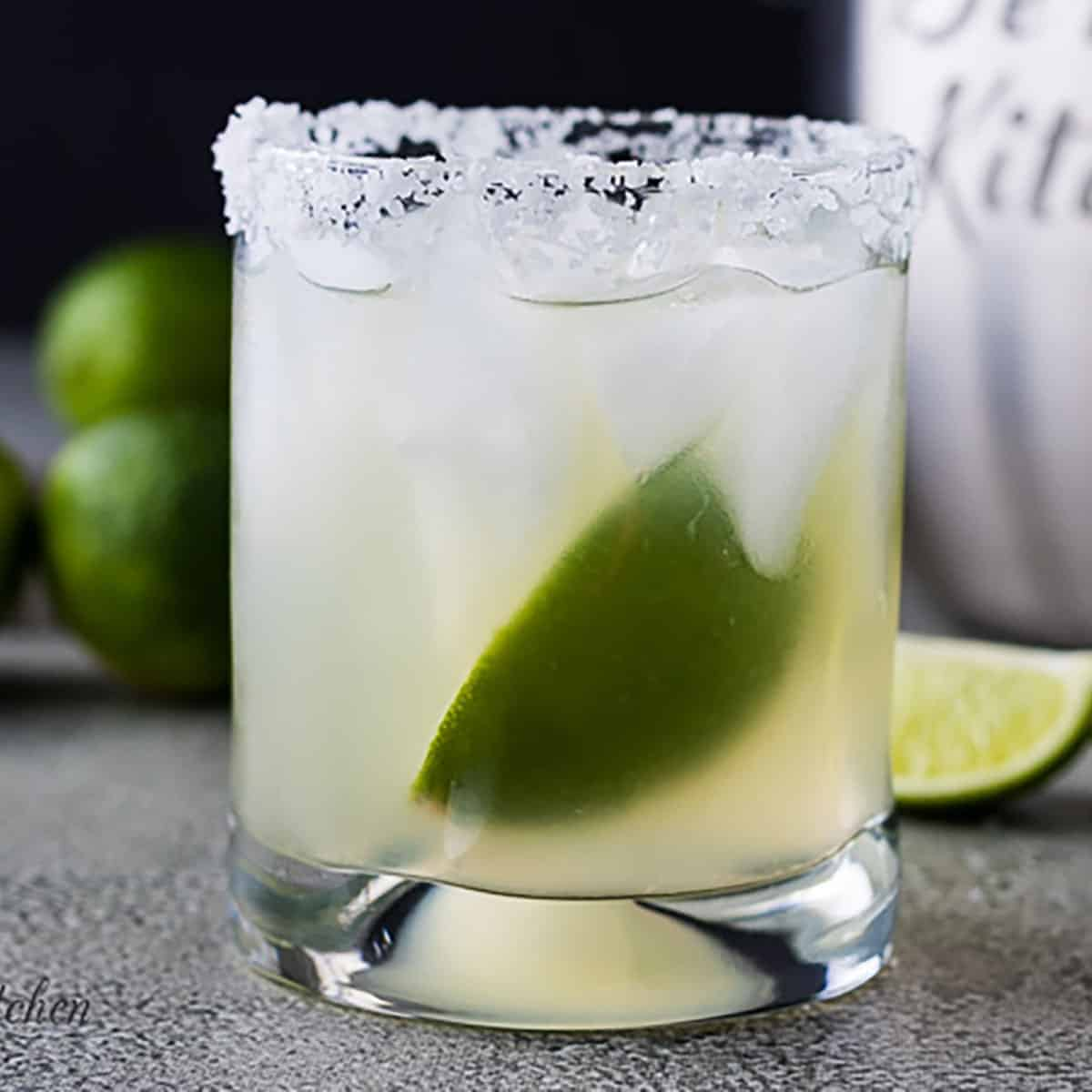 Simple margarita in a salted glass with fresh lime.