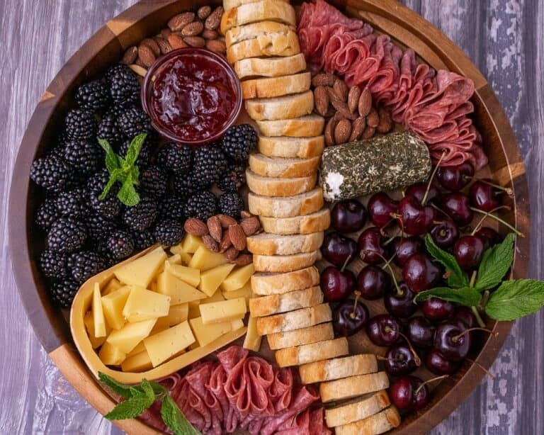 The cheese plate on a wooden platter with fruit and jam.