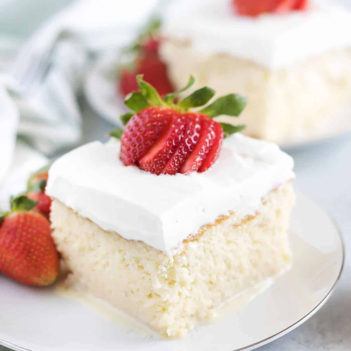 A slice of tres leches cake topped with strawberries on a plate.