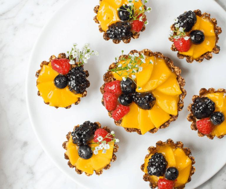 Seven fruit tarts on a round serving platter.