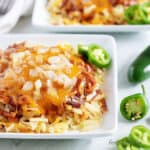 Plate of hash browns covered with chili, cheese, and diced onions next to sliced jalapenos.
