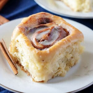 Homemade cinnamon roll on a plate with a cinnamon stick.