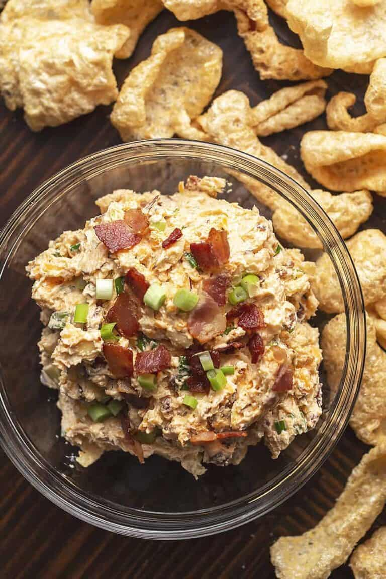The cream cheese dip in a glass bowl with crackers.